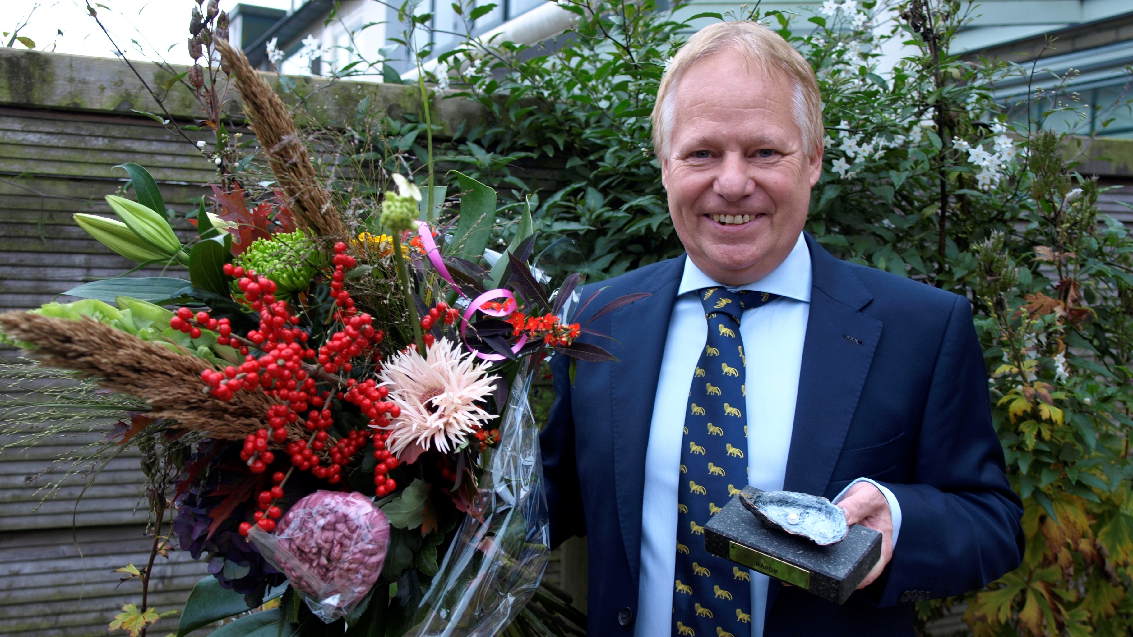 Henk Schallig happy in garden with award